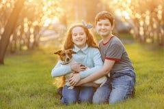 Kinder, die ihren Freund ein Hund im Freien umarmen stockbilder