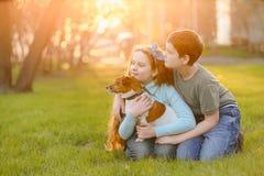 Kinder, die ihren Freund ein Hund im Freien umarmen lizenzfreie stockfotos