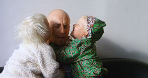 Kinder, die ihren Vater im Wohnzimmer 4k küssen stock footage