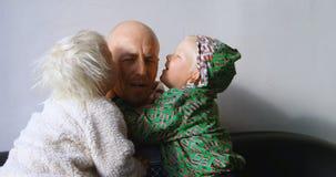 Kinder, die ihren Vater im Wohnzimmer 4k küssen stock video