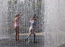 Kinder, die im Brunnen spielen Lizenzfreie Stockfotos