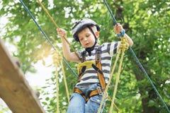 Kinder, die im Erlebnispark klettern Junge genießt, im Seil zu klettern lizenzfreies stockbild