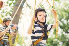 Kinder, die im Erlebnispark klettern Junge genießt, im Seil zu klettern stockbild
