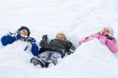 Kinder, die im frischen Schnee spielen Stockfotos