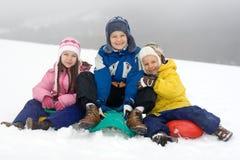 Kinder, die im frischen Schnee spielen Stockbilder