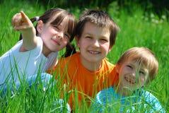 Kinder, die im Gras spielen Lizenzfreie Stockfotos