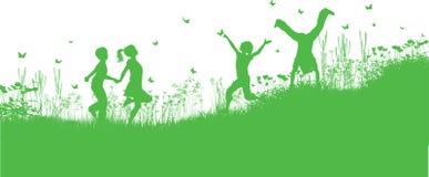 Kinder, die im Gras und in den Blumen spielen Stockbilder