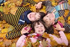 Kinder, die im Herbst spielen Lizenzfreie Stockfotografie
