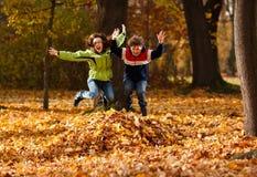 Kinder, die im Herbstpark spielen Stockfotos