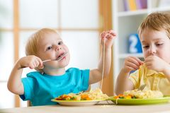 Kinder, die im Kindergarten essen lizenzfreie stockfotos