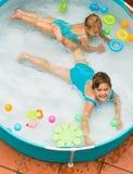 Kinder, die im Kinderpool schwimmen Lizenzfreies Stockfoto