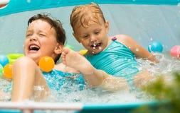 Kinder, die im Kinderpool schwimmen Lizenzfreie Stockbilder