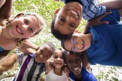 Kinder, die im Kreis um die Kamera umfassen Stockfotografie