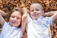 Kinder, die im Laub sitzen Lizenzfreies Stockfoto