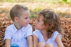 Kinder, die im Laub sitzen Stockbilder
