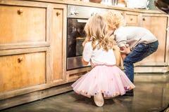 Kinder, die im Ofen schauen stockfoto