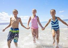 Kinder, die im Ozean spritzen und spielen Lizenzfreie Stockfotos