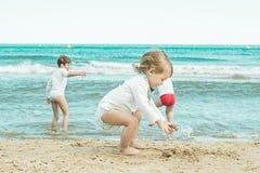 Kinder, die im Sand auf dem Strand spielen Kleinkinder, die auf dem Strand spielen Lizenzfreie Stockfotografie