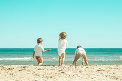 Kinder, die im Sand auf dem Strand spielen Kleinkinder, die auf dem Strand spielen Stockbild