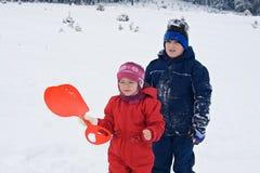 Kinder, die im Schnee bleiben Lizenzfreie Stockfotos