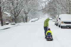 Kinder, die im Schnee mit einem Schlitten spielen Stockfotos