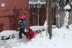 Kinder, die im Schnee spielen Lizenzfreie Stockfotos