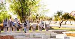 Kinder, die im Skulpturenpark in Vorstadt-Soweto-Nachbarschaft spielen stockbild