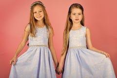 Kinder, die im Sommerkleid spielen Glückliche Kinder, die Spaß zuhause haben Kleine Mädchen auf rosa Hintergrund Stockfotografie