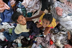 Kinder, die im Stapel von Kleidung spielen Lizenzfreies Stockbild