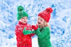 Kinder, die im Wald des verschneiten Winters spielen Lizenzfreies Stockfoto