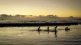 Kinder, die im Wasser auf dem Strand spielen Lizenzfreies Stockbild