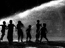 Kinder, die im Wasser spielen stockfotos
