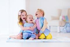 Kinder, die im weißen Schlafzimmer spielen Stockfotos