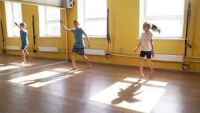 Kinder, die körperliche Bewegungen in einer Turnhalle tun stock footage