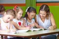 Kinder, die in Kindergarten zeichnen lizenzfreie stockbilder