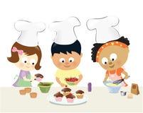 Kinder, die kleine Kuchen backen Lizenzfreie Stockfotos