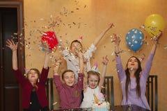 Kinder, die Konfettis an einem children& x27 werfen; s-Partei Kinder haben Spaß zusammen auf einem Familienurlaub Lizenzfreies Stockbild