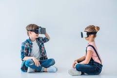 Kinder, die Kopfhörer der virtuellen Realität beim Sitzen auf dem Boden verwenden Lizenzfreies Stockfoto
