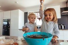Kinder, die Kuchenteig in der Küche vorbereiten lizenzfreie stockfotos
