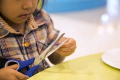 Kinder, die Kunstgegenstand auf Tabelle schneiden lizenzfreie stockbilder