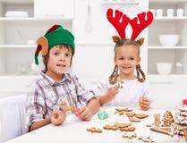 Kinder, die Lebkuchenweihnachtsplätzchen verzieren Stockfotografie
