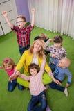 Kinder, die Lehrer umarmen lizenzfreies stockfoto
