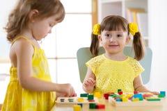 Kinder, die lernen, Formen in Kindergarten oder Kindertagesstätte zu sortieren lizenzfreie stockfotografie