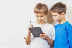 Kinder, die lernen, mit Stift der grafischen Tablette und des Griffels zu zeichnen stockbilder