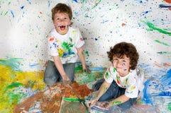 Kinder, die mit Anstrich spielen Stockbild