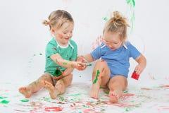 Kinder, die mit Anstrich spielen Stockbilder