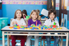 Kinder, die mit Bau-Blöcken herein spielen Stockfotos