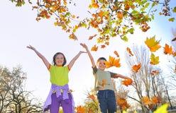 Kinder, die mit Blättern spielen Lizenzfreie Stockfotos