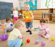 Kinder, die mit Bällen im Kindergartenraum spielen Stockbilder