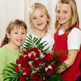 Kinder, die mit Blumen auf Mutter warten Lizenzfreie Stockbilder